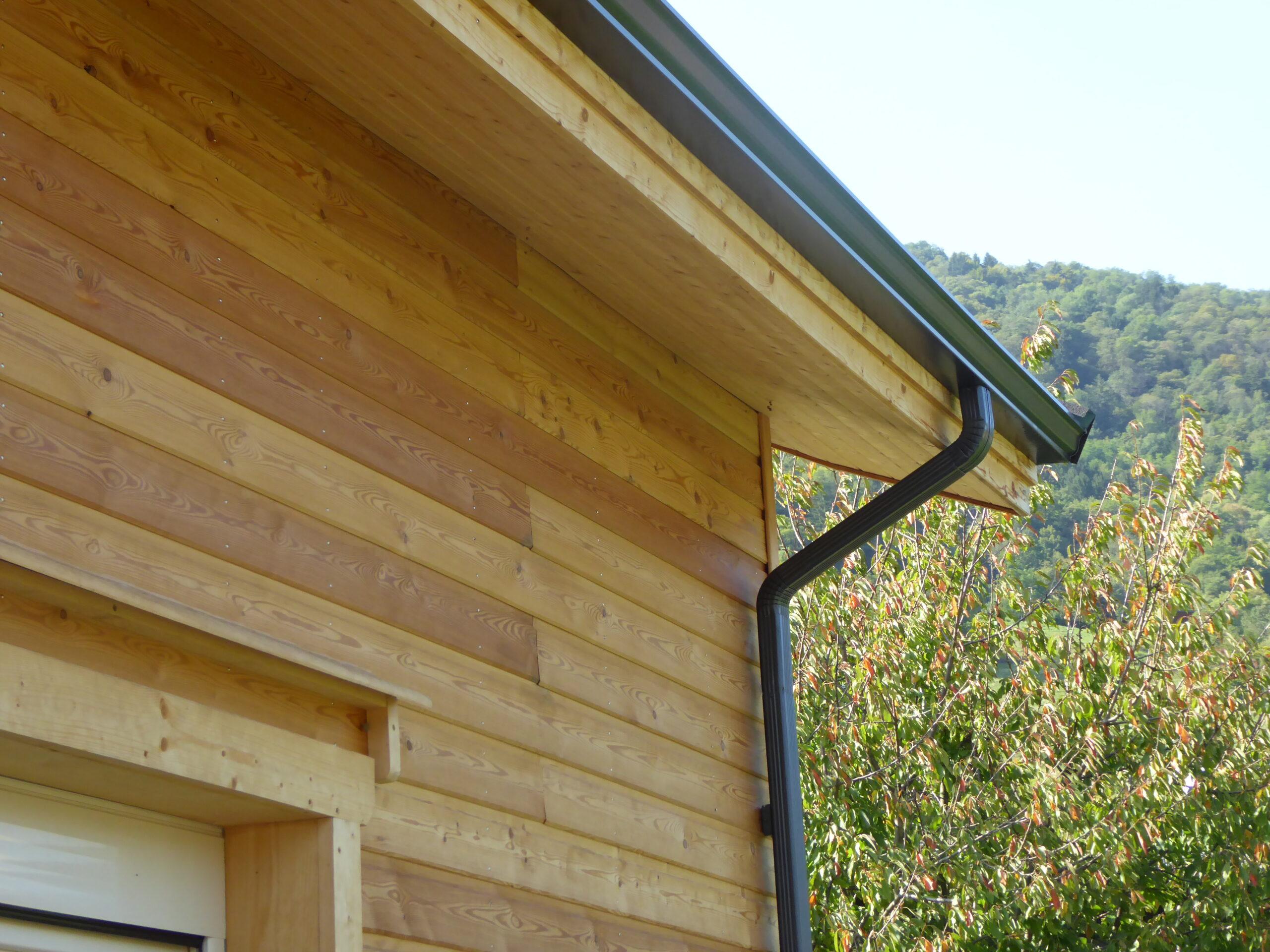 Instalación de canalones sobre una casa de madera.