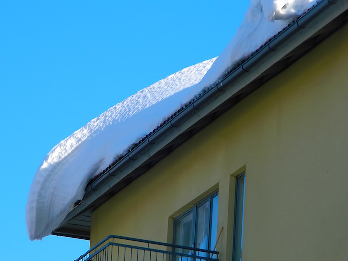 Primera nevada sobre las canaletas pluviales de una casa