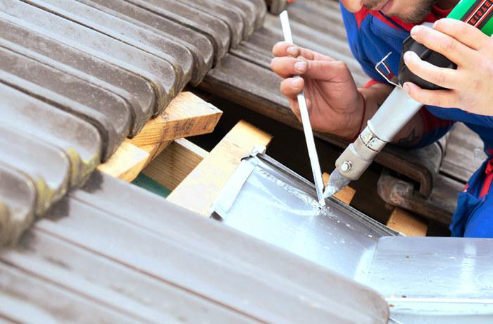 Instalador de canalones haciendo la soldadura de conductos de zinc